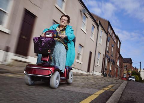 Image of a lady using a mobility scooter