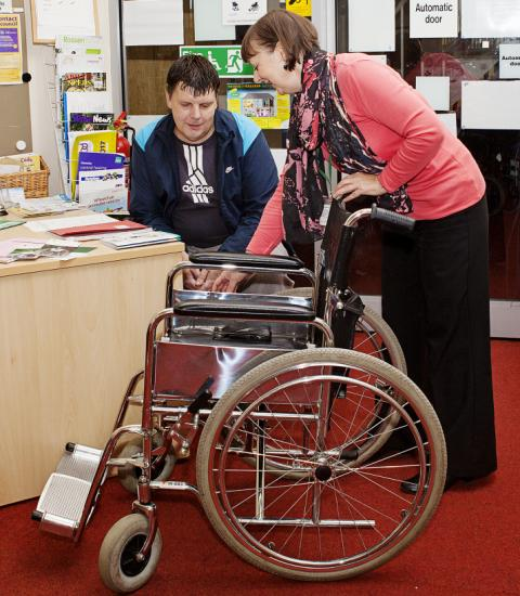 A volunteer demonstrating use of a wheelchair